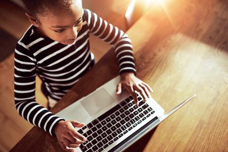 mecanografía: chica negro étnica joven que se sienta en la mesa de comedor en casa escribiendo en un ordenador portátil, vista de ángulo alto mirando hacia abajo en el teclado