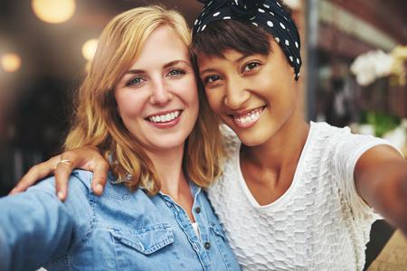 amigos abrazandose: Dos mujeres jóvenes mejores amigos sentados codo con codo con sus caras muy juntas sonriendo a la cámara, multiétnica
