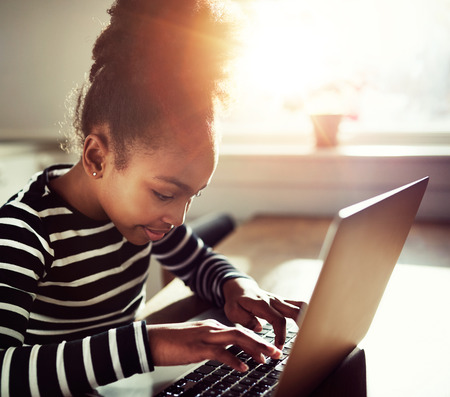 topknot: young black girl with a fun afro topknot concentrating as she types on a laptop computer, close up side view with sun flare back lighting