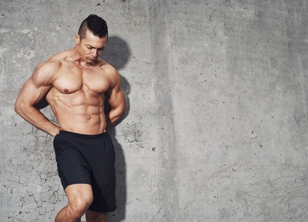 restitution: Male fitness model with abdominal muscles standing on grey background with room for text copy space.