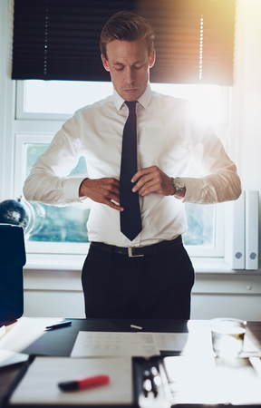 paralegal: CEO executive business type white male tying his tie while standing at desk at his office, success concept