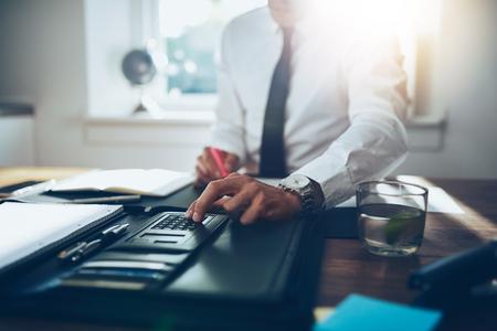 fermer, homme d'affaires ou un comptable avocat travaillant sur des comptes à l'aide d'une calculatrice et de l'écriture sur les documents