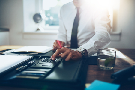 close up, business man or lawyer accountant working on accounts using a calculator and writing on documents Archivio Fotografico