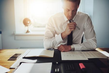 Mit ernster Miene Geschäftsmann arbeitet an Dokumenten mit Aktenkoffer und Handy auf dem Tisch konzentriert
