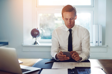Executive business man texting on his phone and checking mail while sitting at his desk at the office