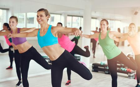 Jonge vrouwen in kleurrijke sportkleding die in aerobicsklasse uitwerken bij de gymnastiek met nadruk aan een glimlachende slanke dame in de voorgrond Stockfoto