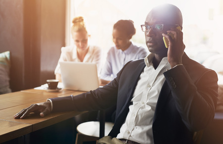 experienced: Black business man using cell phone, white and black business woman in background