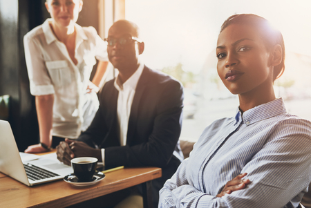 Confident young black business woman sitting in front of other business people