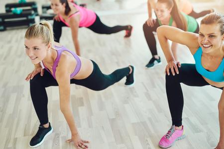 피트 니스, 스포츠, 교육 및 라이프 스타일 개념 - 체육관에서 스트레칭 웃는 여자의 그룹 스톡 콘텐츠