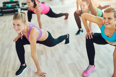 perfect: fitness, sport, training and lifestyle concept - group of smiling women stretching in gym