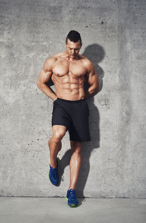 restitution: Fitness model standing against grey background, no shirt showing abdominal muscles, close up, fitness concept advertising Stock Photo