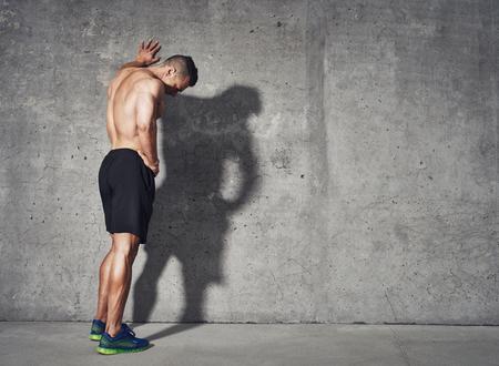 Jongeman rusten na een actieve fitness training terwijl je tegen grijze muur met exemplaar ruimtegebied voor uw SMS-bericht, tevreden geschikt mannelijk man rust na een actieve fitness training