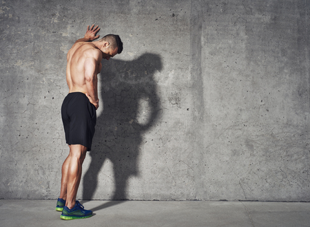 Young man resting after an active fitness training while standing against gray wall with copy space area for your text message, satisfied fit male man resting after an active fitness training