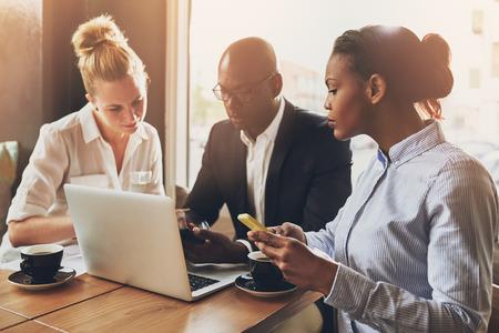professionnel: entrepreneurs ethniques multi planifient leur travail en utilisant un ordinateur portable et un téléphone cellulaire