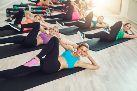 Group of fit healthy young women in a gym wearing colorful sportswear working out in an aerobics class in a healthy active lifestyle concept