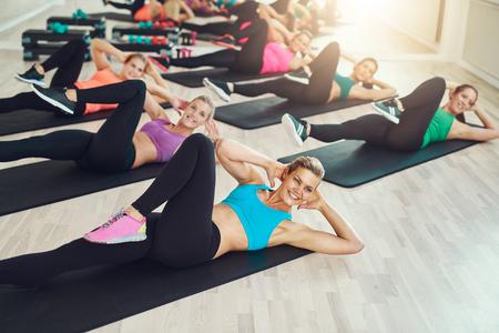 ropa deportiva: Grupo de mujeres jóvenes sanas y en forma en un gimnasio usando colores de elaboración de ropa deportiva en una clase de aeróbic en un concepto de estilo de vida activo y saludable
