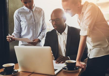 biznes: Etniczne ludzi biznesu, przedsiębiorców pracujących razem przy użyciu komputera przenośnego