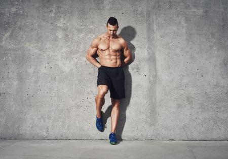 Fitness model staan tegen de grijze achtergrond, geen shirt met buikspieren, ruimte voor kopie ruimte, fitness concept reclame
