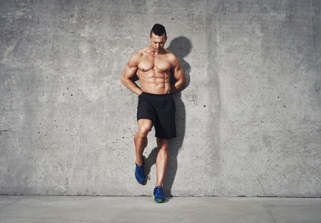 restitution: Fitness model standing against grey background, no shirt showing abdominal muscles, room for copy space, fitness concept advertising