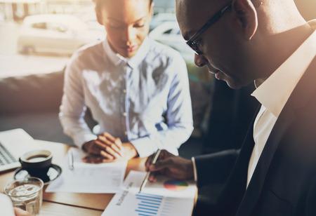 negro: Dos hombres de negocios negro en discusiones sobre su negocio usando tablas para demostrar su éxito