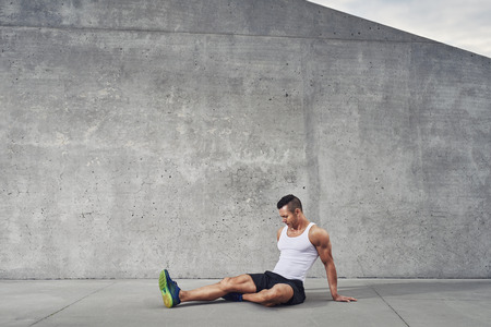 Fitness athlete man relaxing and stretching muscles and legs wearing a white tank top, well build, copy space