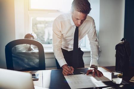 Geschäftsmann, der am Schreibtisch arbeiten an Dokumenten, weißem Hemd und Krawatte, männliche Führungskraft