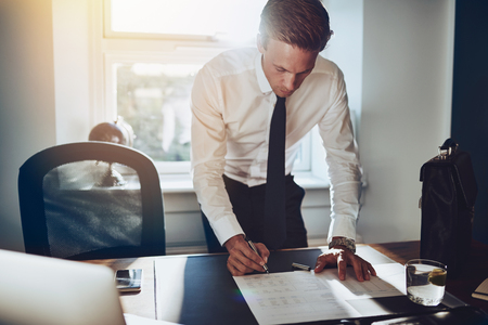 firmando: Hombre de negocios de pie en mesa de trabajo en documentos, camisa y corbata blanca, ejecutivo masculina