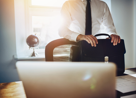 paralegal: Business concept, man standing at desk with briefcase and laptop wearing a classic business outfit
