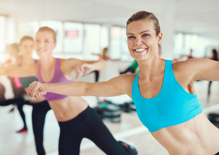 female fitness: fitness, sport, training, gym and lifestyle concept - group of smiling people exercising in the gym