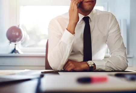Primo piano di uomo d'affari seduto alla sua scrivania a parlare al telefono
