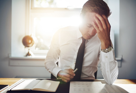 Business man working concentrated on documents looking tired holding his hand to his forehead