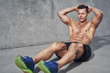 Male fitness model doing sit ups and crunches exercising abdominal muscles, six pack visible wearing no shirt. Stock Photo