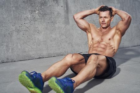 modelos hombres: Modelo masculino de la aptitud haciendo sentadillas y abdominales que ejercen los músculos abdominales, abdominales visibles lleva sin camisa