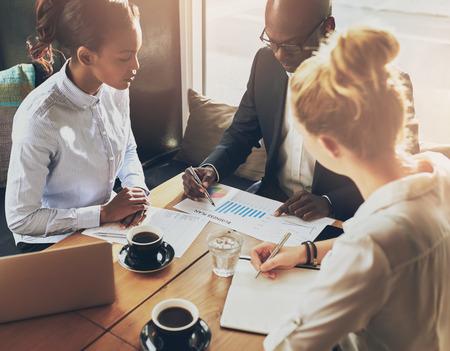 Gli uomini d'affari che parlano le tabelle e grafici che mostrano i risultati del loro lavoro di squadra di successo, business multi etnica