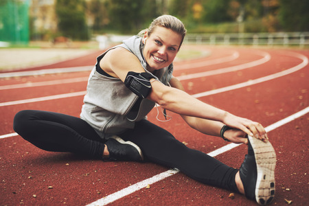 woman stretching: Young sportswoman sitting and stretching on track field while listening to music, looking at camera. Stock Photo