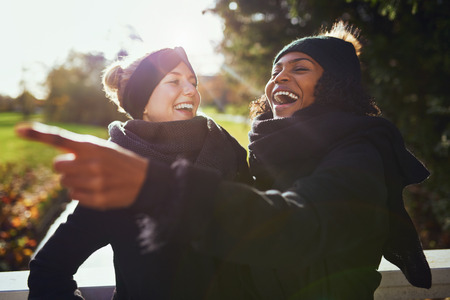 to get warm: Two women laughing at something while standing in park Stock Photo