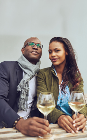 the trendy: Portrait of black couple dating, sitting on a coffee shop outside Stock Photo