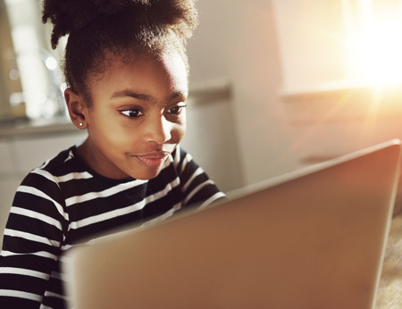 adolescent: Smiling black girl using a laptop at home sitting reading information on the screen with an absorbed expression and a smile of pleasure