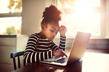 chica pensando: Niña sentada en la mesa de comedor en casa trabajando en su tarea de la escuela escribiendo a cabo una respuesta en un ordenador portátil, el concepto de e-learning
