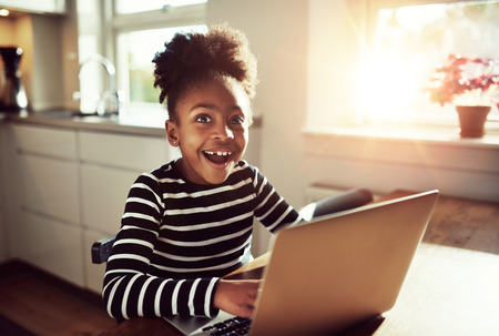 Black girl sitting playing on a laptop computer at home looking at the camera with a joyful expression of amazement and wonder