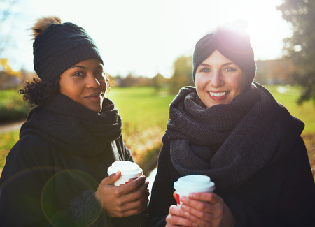 to get warm: Two young women looking at camera, smiling while holding coffee to go against of autumnal park Stock Photo