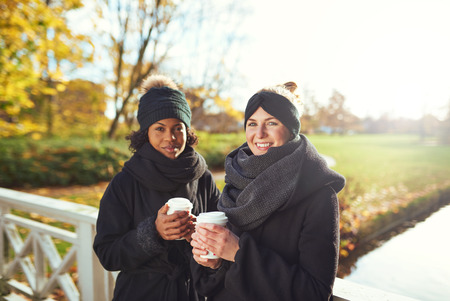 to get warm: Two young women standing on bridge and holding coffee to go, smiling
