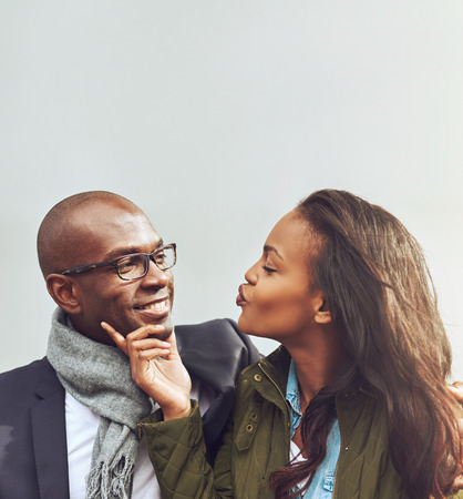 puckered lips: Loving African American couple on a date flirting together as the young woman puckers up her mouth for a kiss while caressing the mans chin