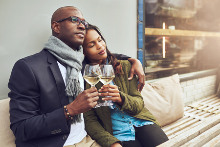 american content: Romantic loving couple enjoying each others company sitting relaxing on a wooden restaurant bench in a close embrace drinking white wine