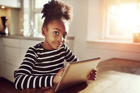 Durchdachtes junges schwarzes Mädchen, das die Kamera mit einem nachdenklichen Ausdruck aufpassend sitzt, wie sie das Internet auf einem Tablet-Computer zu Hause durchstöbert