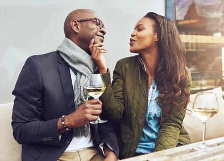 aniversario: Joven atractiva mujer afroamericana coquetear con su novio frunciendo los labios para un beso y le acaricia la barbilla