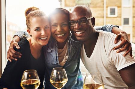 Tres étnicos amigos sonriendo a la cámara y abrazos Foto de archivo