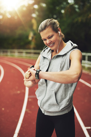 track and field athlete: Portrait of  blonde athlete looking at her watch, smiling and listening to music while standing on track field