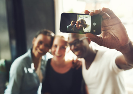 threesome: Multi ethnic friends taking a selfie with a phone