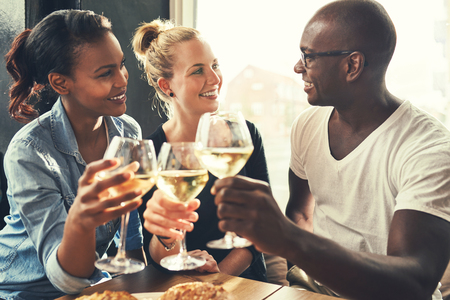Ethnic friends at a bar drinking wine and eating tapas Foto de archivo